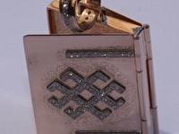 Apraksts : Atverams kulons ar latvju zīmēm un Briljantiem, Materiāls : Baltais Zelts un Sarkanais Zelts